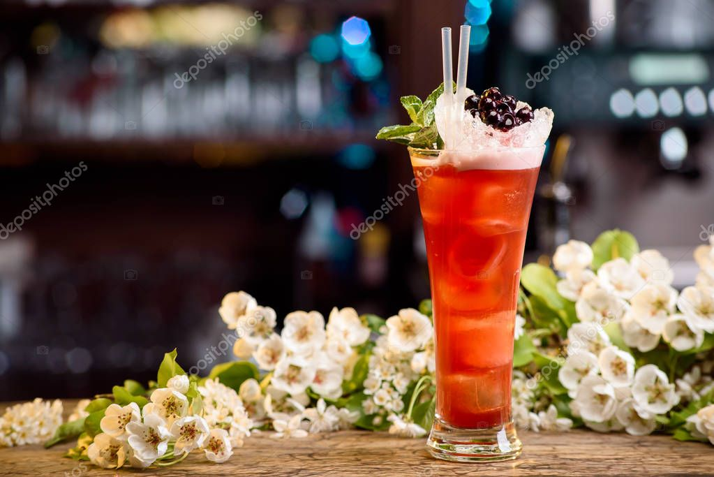 summer cocktail with ice decorated with berries and mint on a wooden table