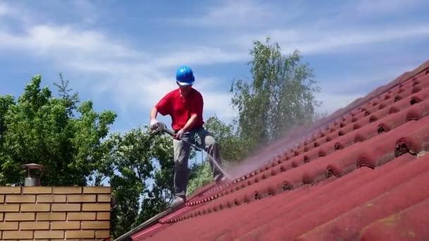 Čištění střešního přístroje pomocí nástroje pro tlak vody. Pracovník na vrcholu stavebních prací s profesionálním vybavením. Odstraňování mechu.