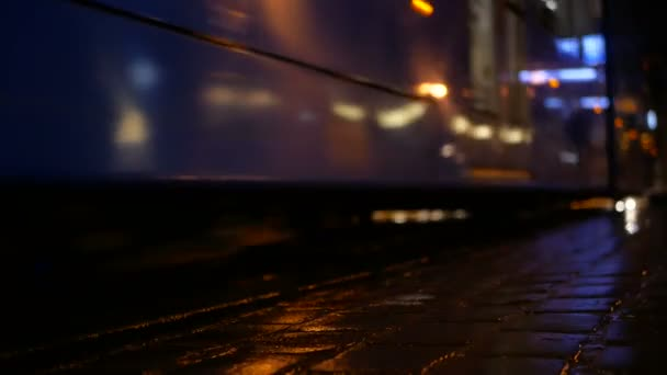 Night time video of trams and people in rain city