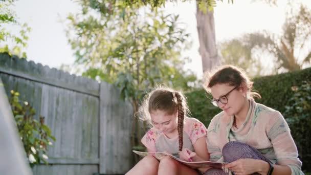 Glücklich lächelnde Mutter und Kind Spaß und Zeichnen von Bildern im Freien im Garten im Sommer. zusammen