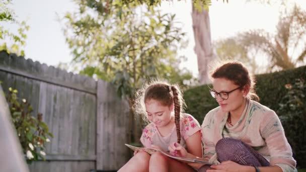 Glücklich lächelnde Mutter und Kind Having Fun und Zeichnung Bilder draußen im Garten im Sommer-Sonne