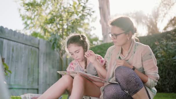 Glücklich lächelnde Mutter und Kind Having Fun und Zeichnung Bilder draußen im Garten im Sommer Midl erschossen