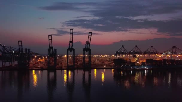 Aerial drone. Flight up container port with ships and cranes at Night