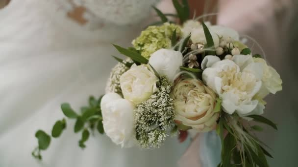 Beautiful bridal bouquet in hands of bride dressed in white wedding dress. Close up
