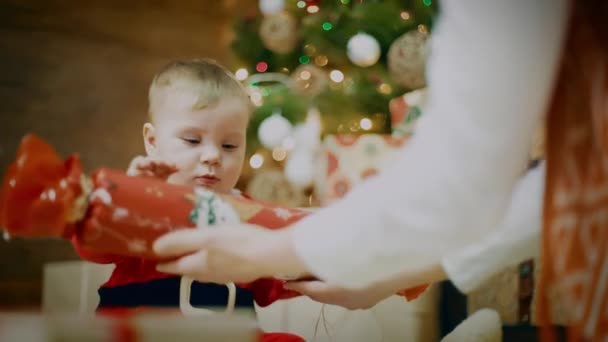 Amazing looked of woman mom giving a gift to her excited cute little boy or girl that clapping her hands near a decorated Christmas tree and gift. Close UP