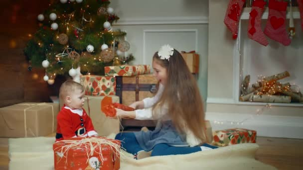 Amazing looked of litle girl giving a gift to her excited cute little boy or girl that clapping her hands near a decorated Christmas tree and gift. midle shot