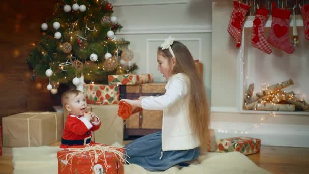 Amazing looked of litle girl giving a gift to her excited cute little boy or girl that clapping her hands near a decorated Christmas tree and gift.