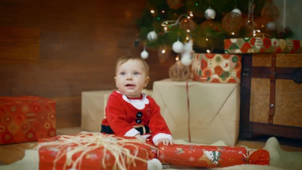 Amazing looked of giving a gift to her excited cute little boy or girl that clapping her hands near and smile a decorated Christmas tree and gift. shot midle