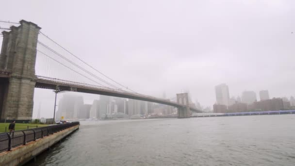Skyscrapers of Manhattan and Brooklyn Bridge, New York City  fog over the  skyscrapers, cloudy weather and traffic on the river  Wide shot  fog day