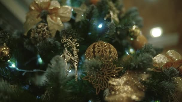 A christmas tree decorated with christmas tree toys and shining lights, gold bokeh effect.
