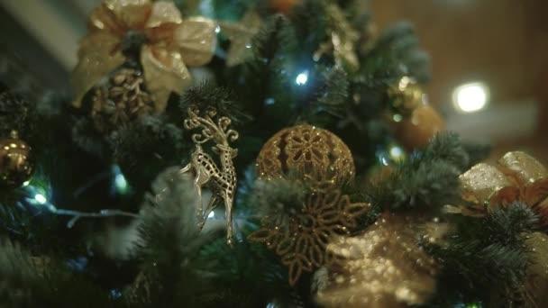 Vánoční strom zdobí vánoční strom hračky a zářící světla, zlaté bokeh efekt.