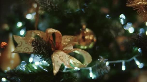Vánoční stromeček zdobený vánoční strom hračky a zářící světla, zlaté bokeh efekt. pohyb kamery