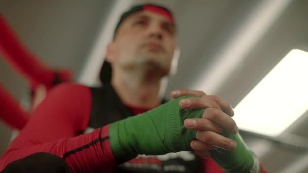 Kämpfer, Boxer, die Handschellen anlegen, während sie auf einem Ring sitzen und sich auf den Kampf vorbereiten. ein Blick