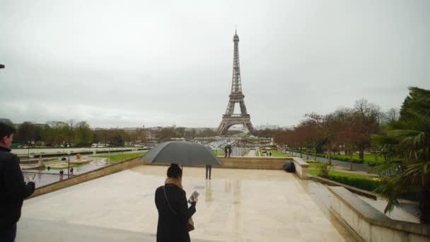 PARIS - september 8, 2018: Eiffel tower view from Trocadero with people with umbrellas, rainy.