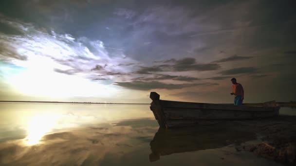Zeitlupe. ein Mann, der auf dem Wasser geht und mit dem Handy Fotos von einem unglaublichen Sonnenuntergang an einem See bei Sonnenuntergang macht.