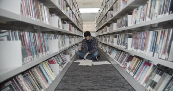 student univerzity sedí na podlaze v knihovně, čte knihu. Zapne stránky knihy. midlová střela