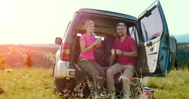 Young man and woman holding cups with drinks and sitting near the car in the mountain during sunny day. V2