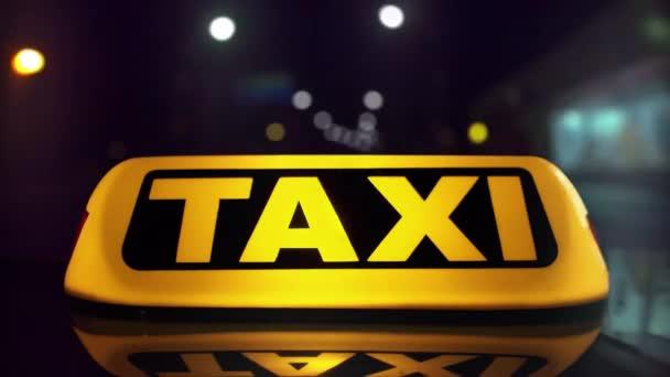 Taxi projíždí městem v noci. Bokeh světla. Detail střešního světla. Načasování. 4k