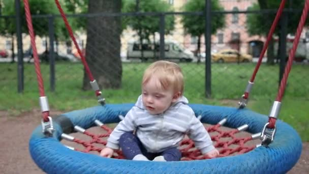 A little boy swings on a swing in a Playground in the Park. Outside