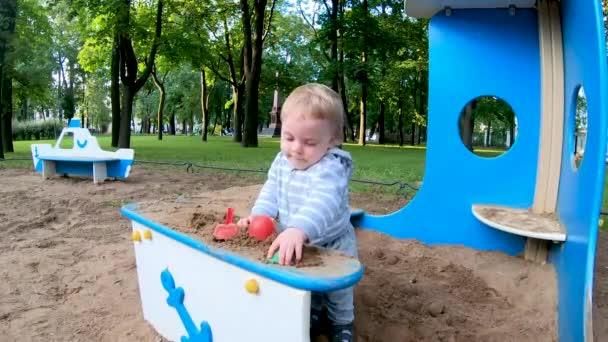 Vtipný malý blonďatý chlapec hrající si s hračkami na pískovišti na hřišti v parku za jasného slunečného dne. Šťastné dětství.