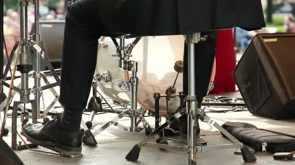 Ein Musiker auf einer Straßenbühne schlägt den Rhythmus mit den Füßen auf einem Hi-Hat-Percussion-Instrument und einer Bassdrum.