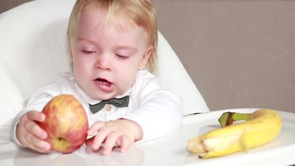 Šťastné malé dítě kouše zralé jablko. Koncept zdravého stravování. Dítě jí jablko a banán v dětské sedačce. Dětská snídaně s čerstvým ovocem