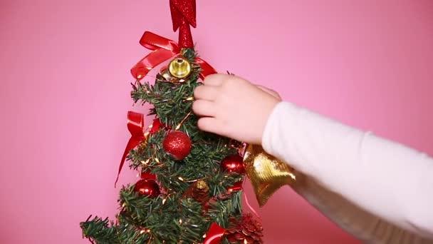 Ein kleines Mädchen mit rotem Weihnachtsmütze schmückt den Weihnachtsbaum mit Weihnachtsspielzeug und Neujahrsgeschenken.