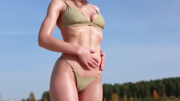 Mladá žena v masážních kombinézách rozmazává opalovací krém na těle v oblasti břicha. Dívka dává opalovací olej na své opálené tělo.