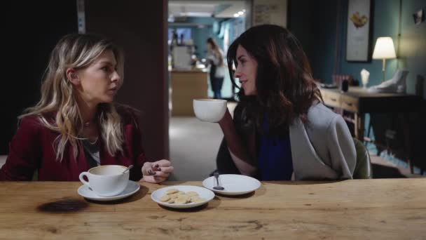 Two young attractive friends talking in a cafe, woman in business concept