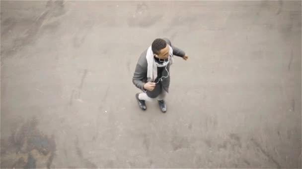 Top view of an African American man dancing in an autumn street, headphones