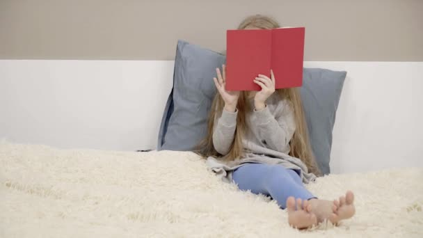 Little girl in a dress and leggings reading a red book sitting on a bed