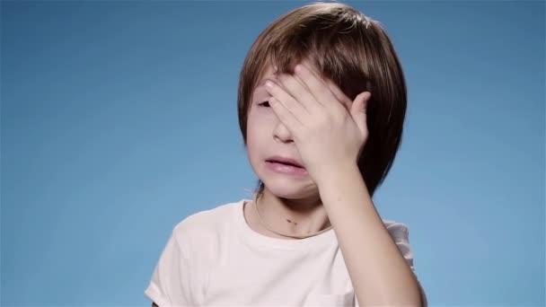 Szuper lassú mozgás a kisfiú dörzsöli a szemét, sírás, vagy fáradt, kék háttér