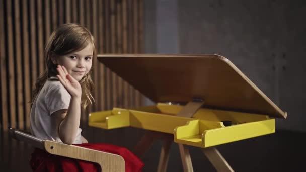 Kislány ül az asztalnál, és integetett a kezét