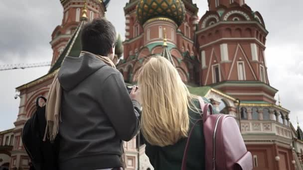 Young tourists couple taking pictures of Moscow cathedral near Kremlin, Russia