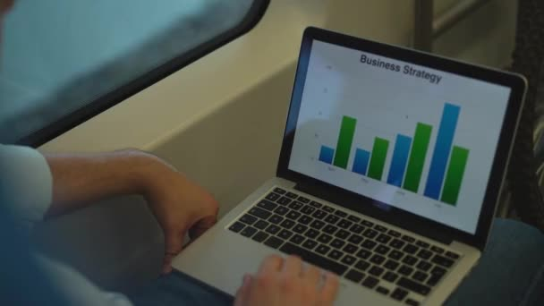 Businessman studying graphs on his laptop in a train