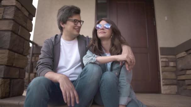 Veselý mladý pár sedí spolu na verandě svého domu a mluví