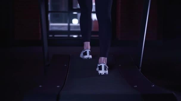 Žena s nohy v bílých teniskách a leginy běhání na běžeckém pásu zadní pohled