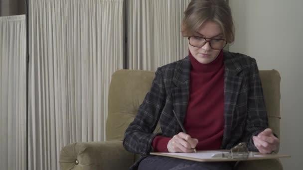 Vážné mladá žena v brýlích, psaní do schránky