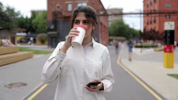 Attractive young girl with coffee and smartphone walking in the summer street