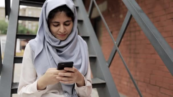 Amazing young woman in hijab sitting on stairs outside and texting, summer
