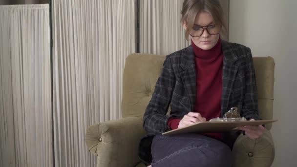 Mladá žena v brýlích, psaní do schránky, sedí v křesle