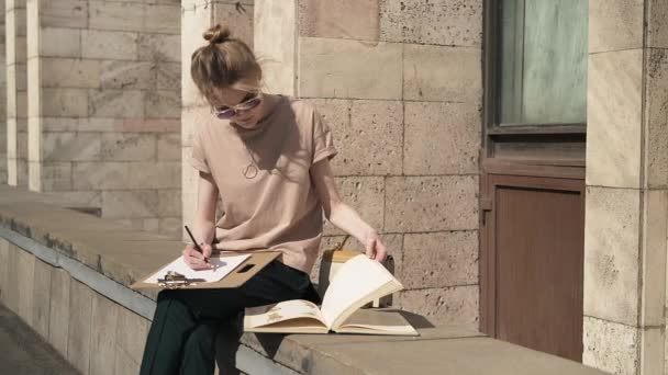 Attractive young woman studying outside