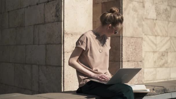 Beautiful young girl studying with laptop and books outside, summer