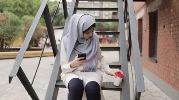 Mladá žena v hidžábu sedí na schodech vně a textilie