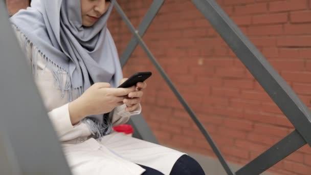 Mladá žena v hidžábu sedí na schodech vně a textových zpráv, naklonění