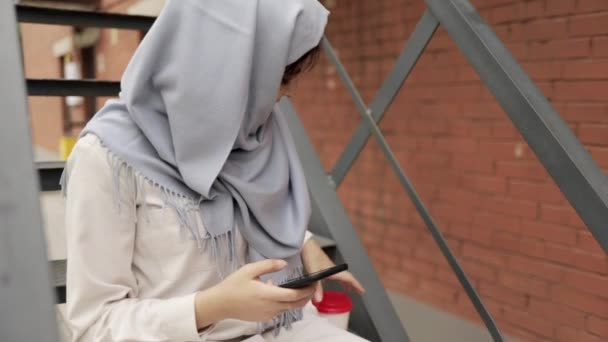 Amazing young woman in hijab sitting on stairs outside and texting
