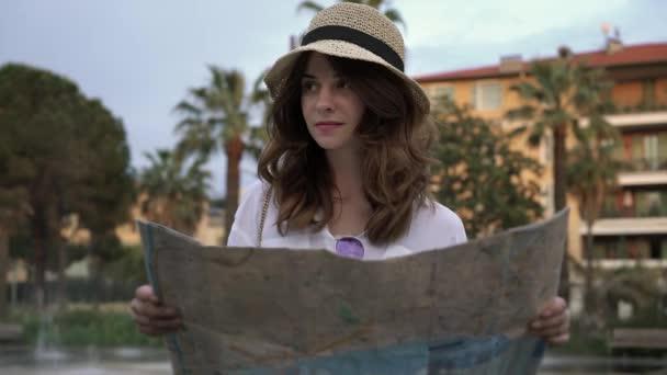 Krásné turistické dívka při pohledu na mapu ve francouzské ulici poblíž fountain