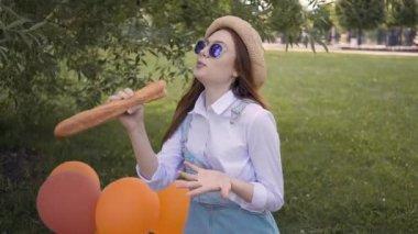 6d963bd8c641f5 Jong meisje gember zingen met behulp van een stokbrood als een microfoon in  park — Stockvideo