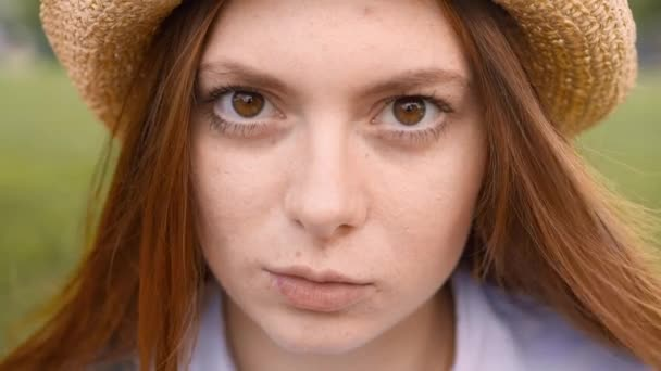 Close up of young ginger woman standing outside looking at camera and blinking