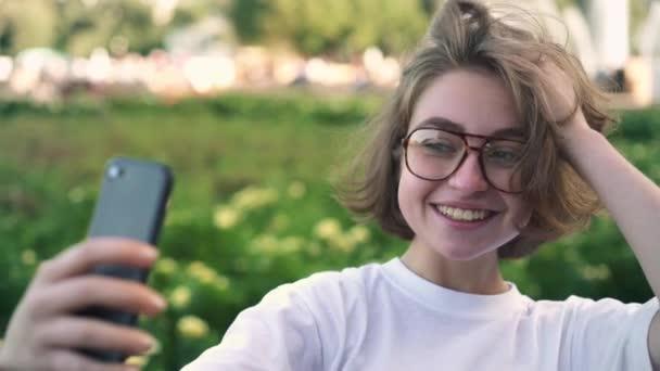 Roztomilá mladá dívka v brýlích, takže v létě parku selfie snímky nebo vlogging